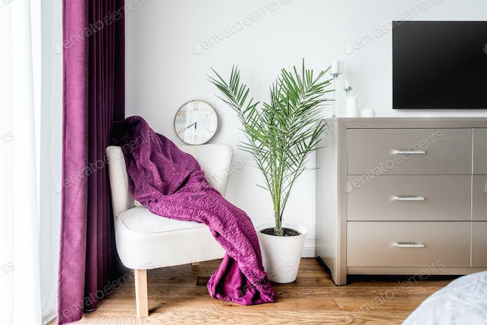 Armchair, purple blanket and a wall clock as decor in modern, stylish bedroom