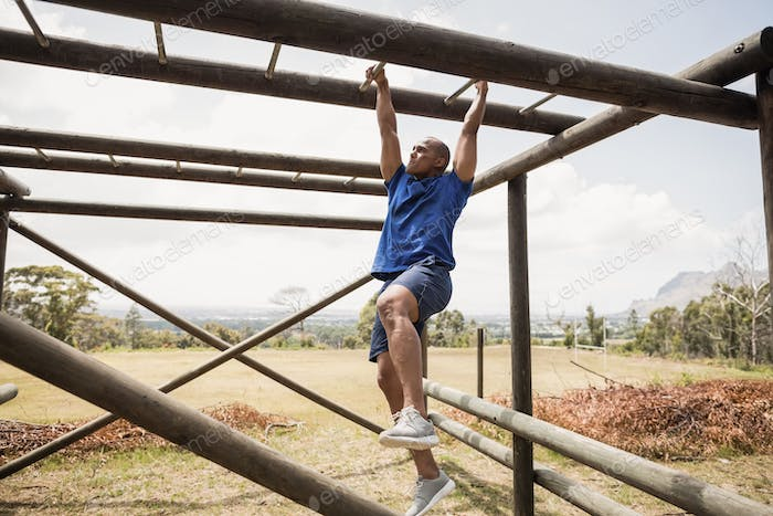 Fit man climbing monkey bars during obstacle course