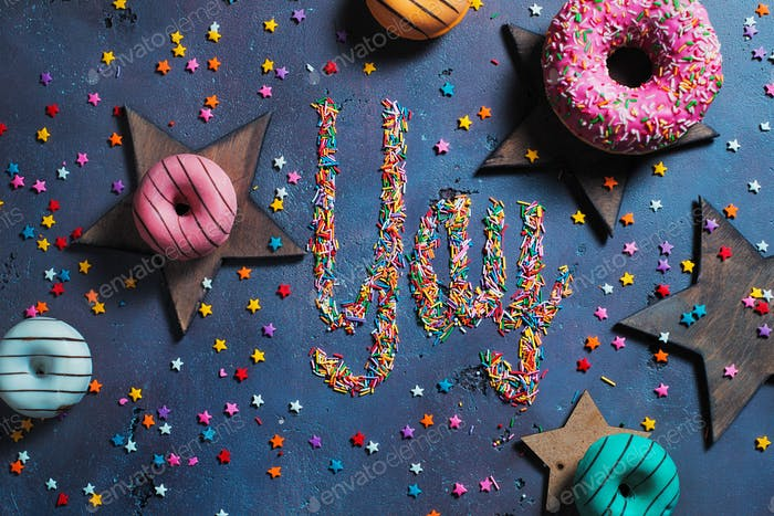 Exclamation Yay written with sprinkles on a stone background with donuts and stars. Party