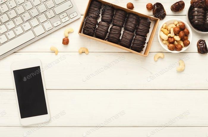 Arbeitsdesktop mit gesunden Süßigkeiten und Nüssen