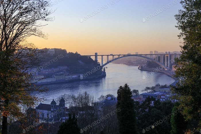 Luis I bridge and small ship sailing the river in Porto, Portuga