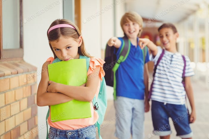 School friends bullying a sad girl in corridor
