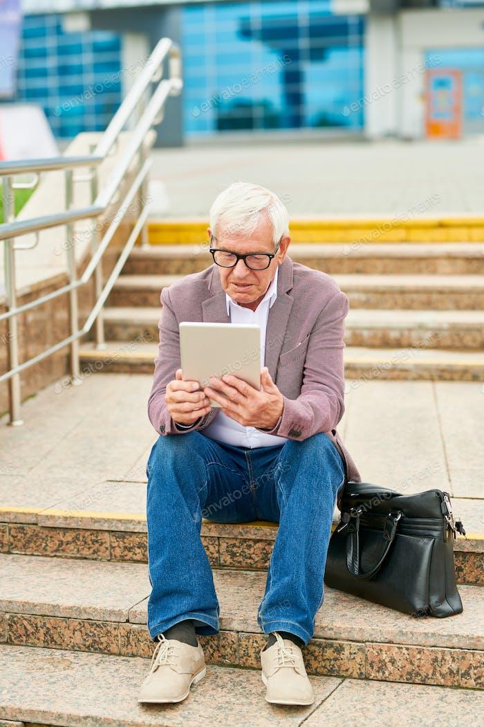 Aged entrepreneur with tablet on steps