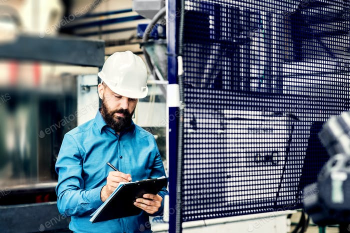 A portrait of an industrial man engineer with clipboard in a factory, working.