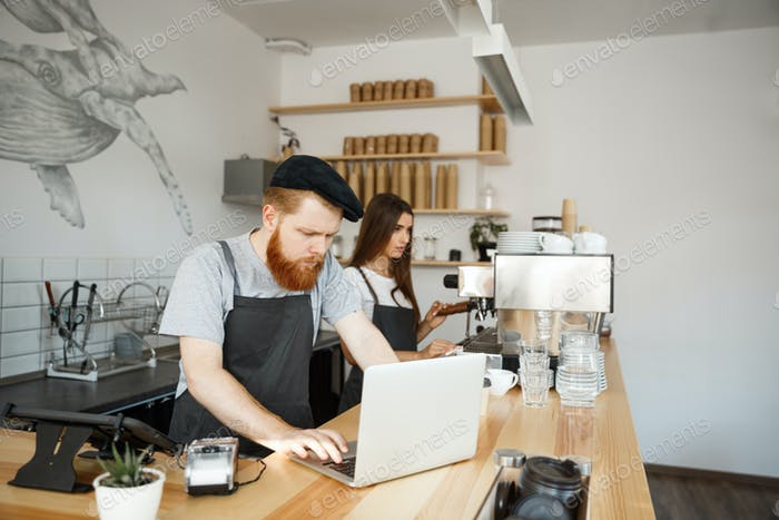 Coffee Business Concept - Young handsome bearded bartender, barista or manager working and planing