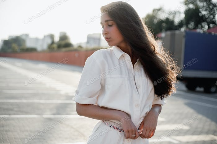 Young girl with long dark hair dressed in white shirt is standing in the street in the bright