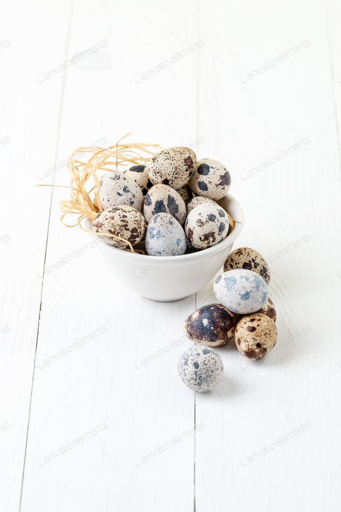 Fresh quail eggs in a white bowl on a white wooden table.