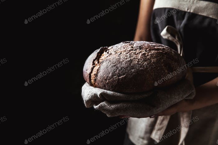 rustic bread in baker hand, healthy food