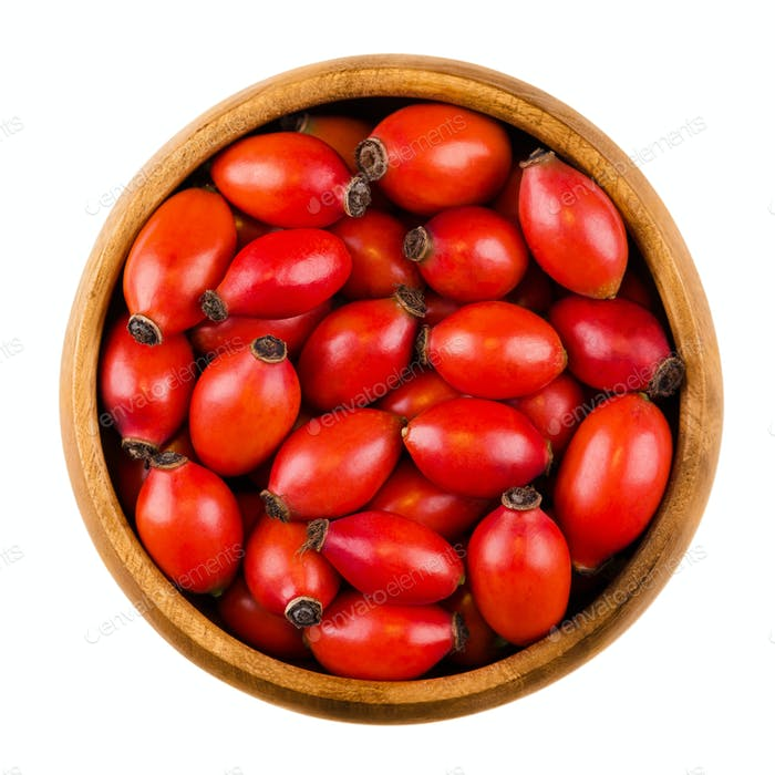 Red rose hips in a wooden bowl over white