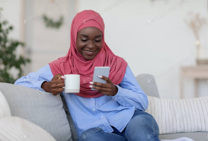 Black Islamic Woman Relaxing On Couch At Home With Smartphone And Coffee