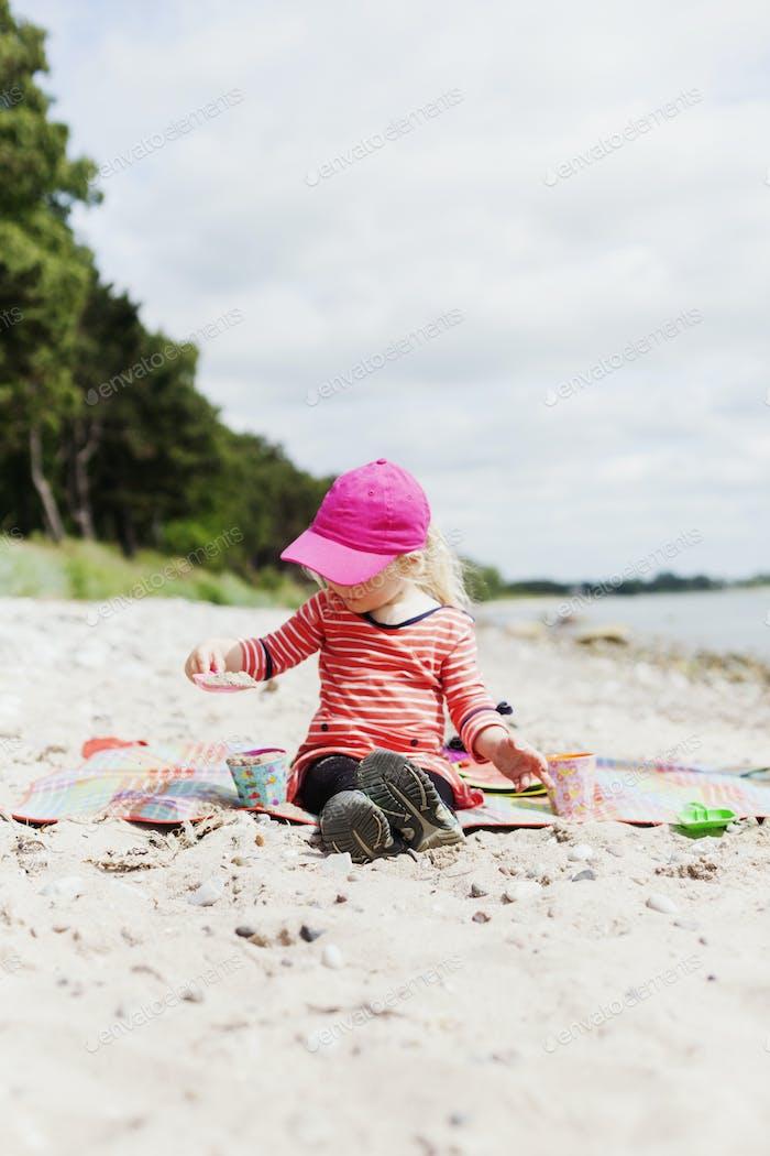 Mädchen spielen mit Spielzeug auf Sand am Strand