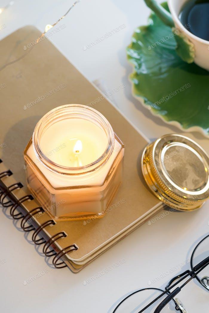 Tasse Tee und aromatische Kerzen auf einem Notizbuch auf einem weißen Tisch