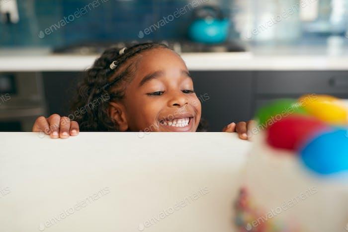 Mädchen versteckt hinter Küchentheke nimmt Sneaky Blick auf Geburtstagskuchen