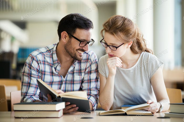 Happy students couple in school library have discussion