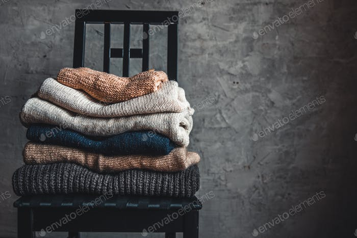 a stack of knitted warm cozy sweaters , on a chair by the gray wall. autumn, winter concept