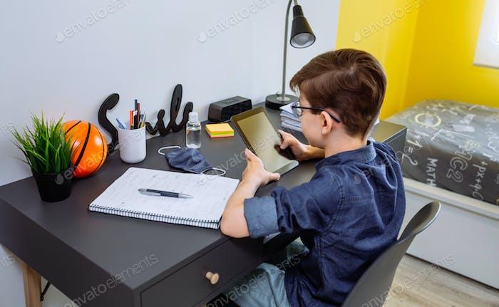 Teenager macht Hausaufgaben mit einem Tablet