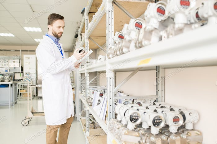 Busy quality control engineer examining manometers in warehouse