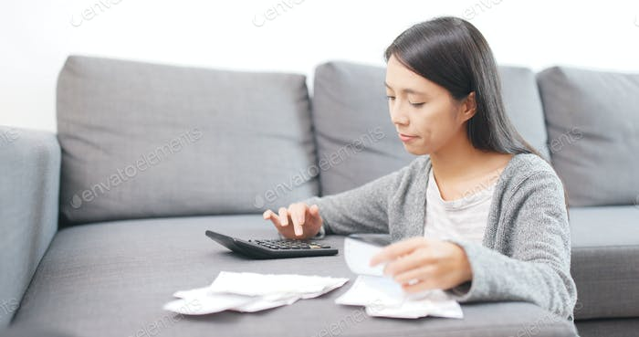 Housewife calculating the expense at home