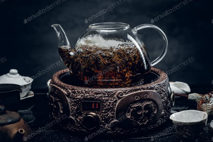 Traditional herbal tea in transparent glass teapot.