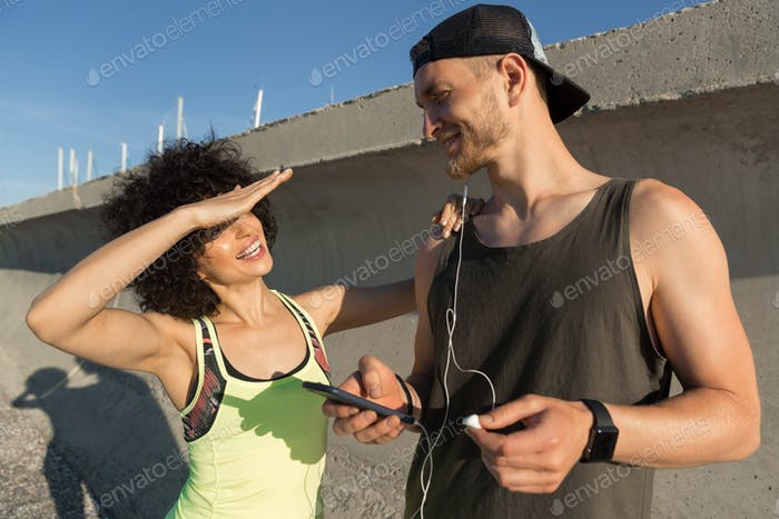 Young fitness couple listening to music with earphones outdoors
