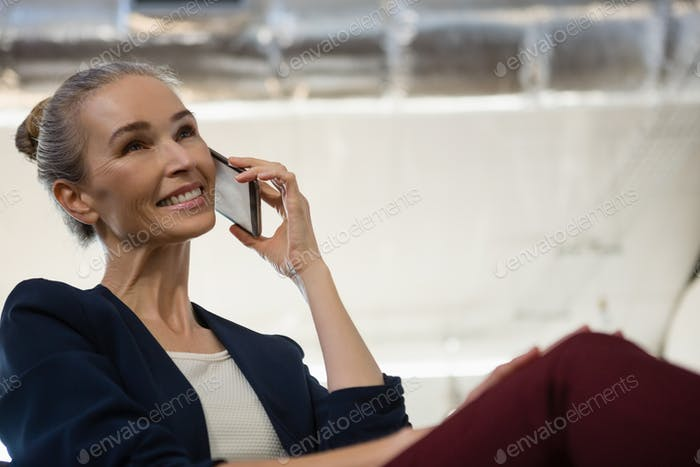 Businesswoman communicating on smart phone at office