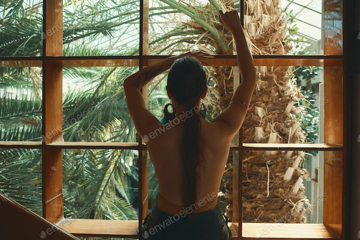 Back view of woman looking through a window to exotic plants