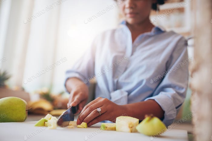 Female hands chopping fruits for juice