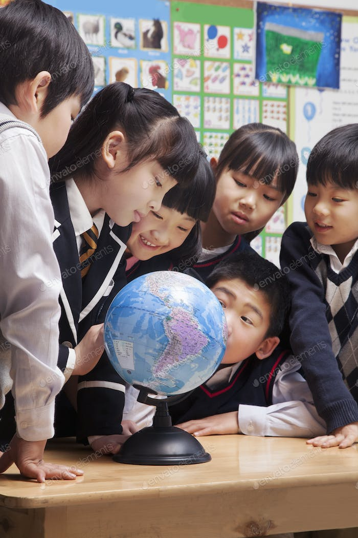 Schoolchildren looking at a globe in the classroom