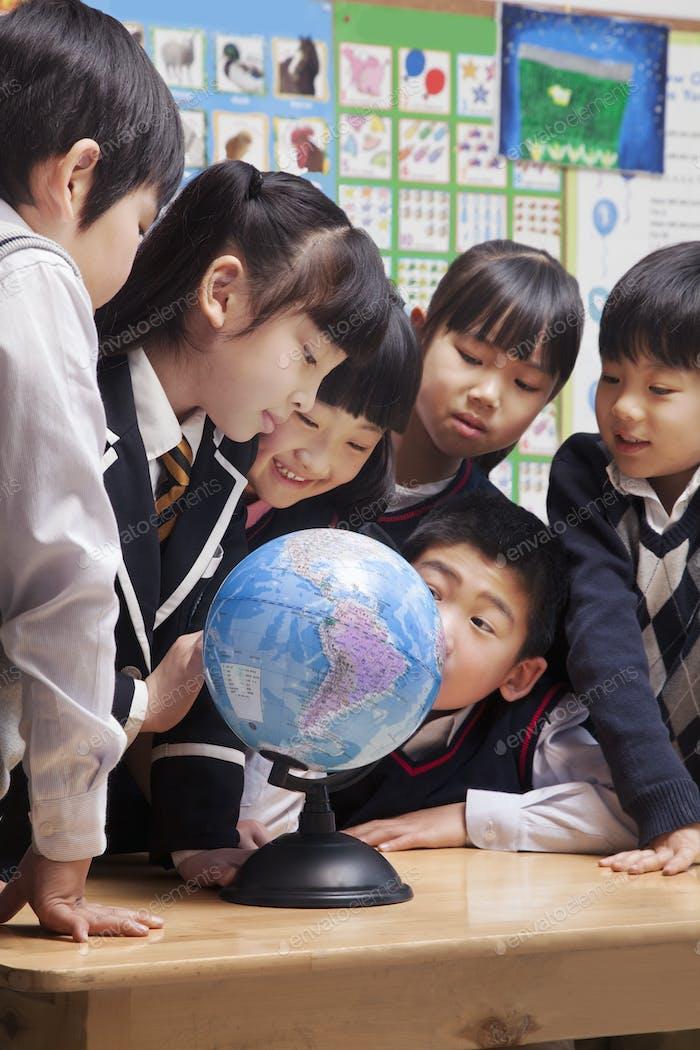 Schulkinder, die einen Globus im Klassenzimmer betrachten