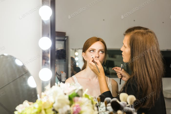 make up artist doing professional make up of young red-haired woman