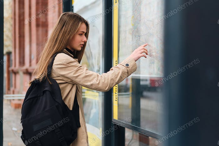 Beautiful casual girl with backpack thoughtfully looking city map on bus stop