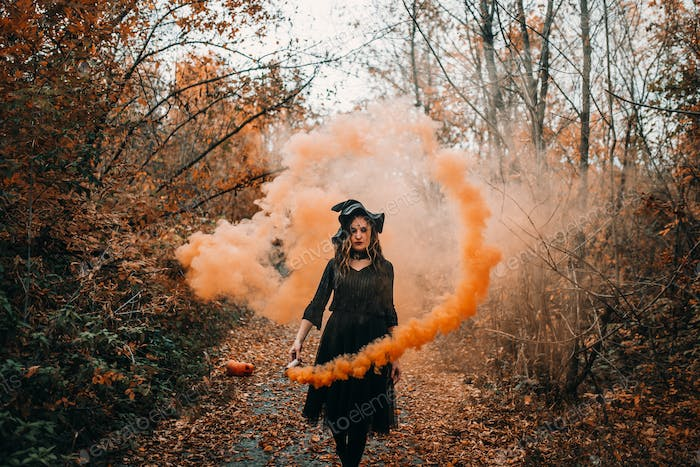 Girl dressed as witch holding smoke bomb in her hands