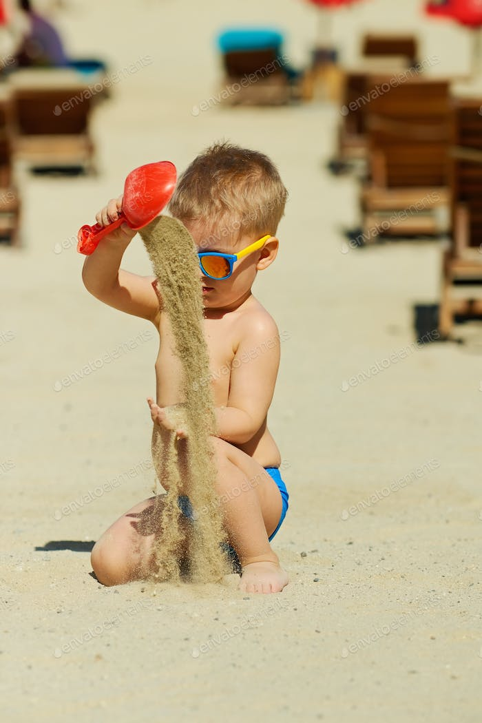 Toddler boy playing with shovel and sand on beach