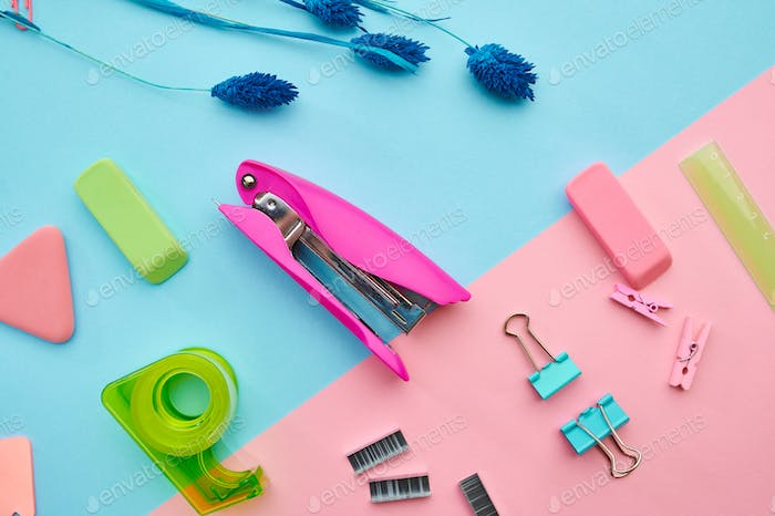 Stapler and clips closeup, blue background