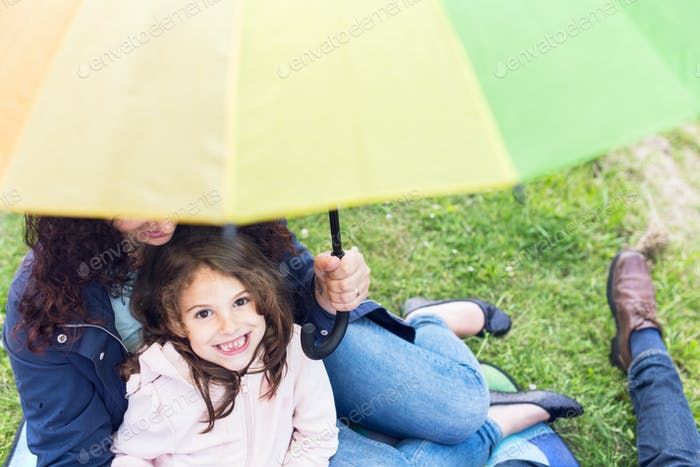 Parents with daughter (4-5) sitting under colorful umbrella