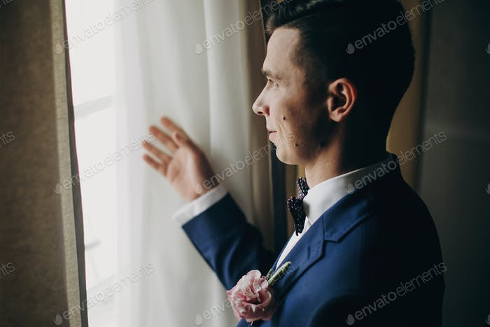 Stylish groom in blue suit, with bow tie and boutonniere