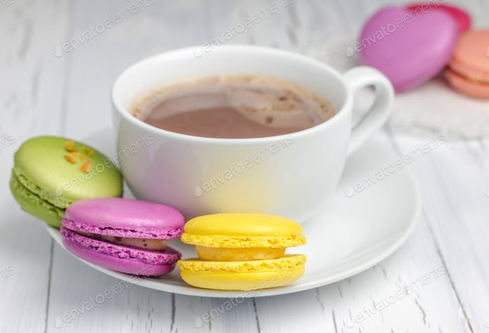 A cup of hot chocolate with colorful macarons closeup