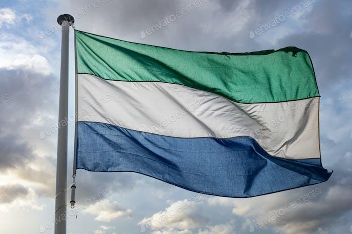 Sierra Leone flag waving against cloudy sky