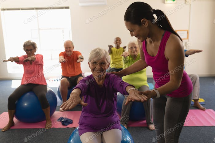 Happy Young female trainer assisting senior woman to do exercice ball in fitness studio