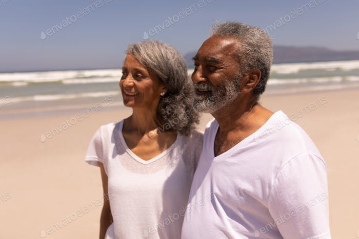 Side view of happy senior couple standing on the beach and looking away in the sunshine