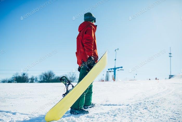 Snowboarder in Brille Posen mit Brett in den Händen