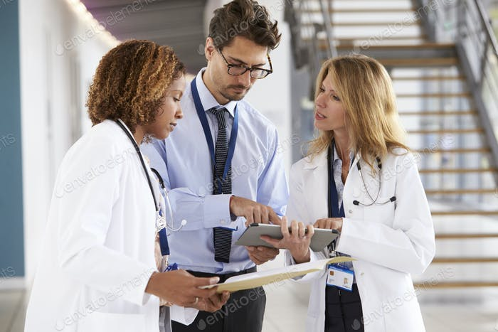 Three young male and female doctors consulting