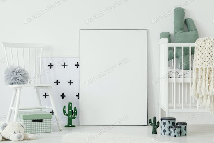 Grey pompom placed on white chair standing in bright baby bedroo