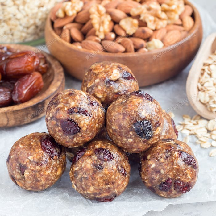 Healthy homemade energy balls with cranberries, nuts, dates and rolled oats on a parchment, square
