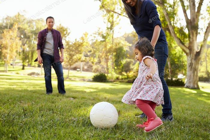 Eltern treten einen Ball mit ihrer jungen Tochter in einem Park