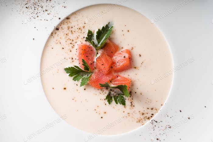 Soup puree from salmon in a porcelain dish