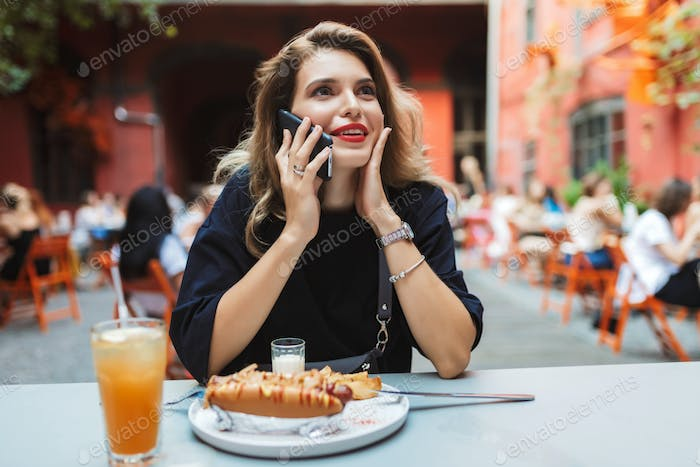 Young pretty smiling woman in black dress sitting at the table w