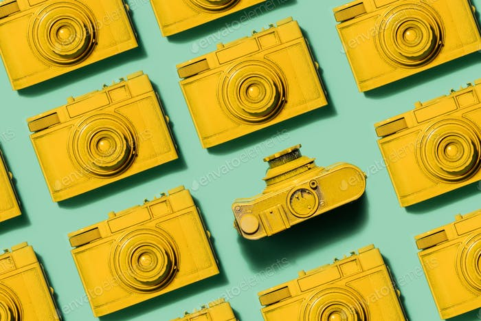 Vintage yellow cameras laying on green background