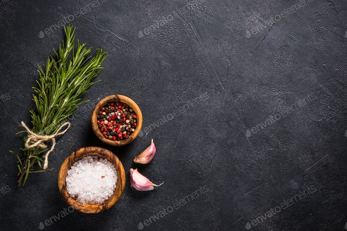 Food cooking background with herbs and spices on black