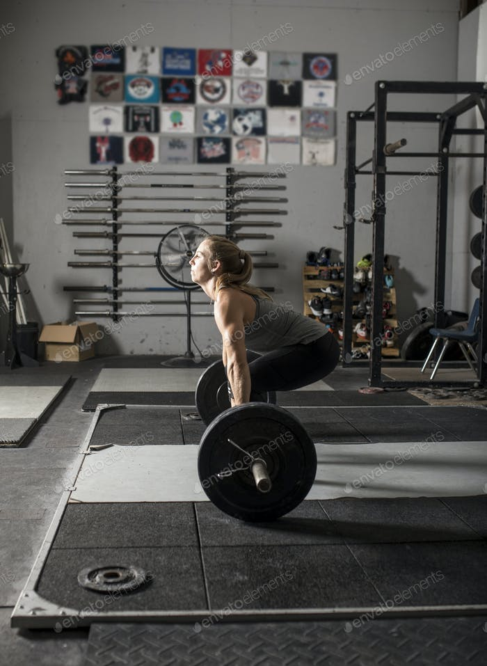 Young strong woman preparing for deadlift in a gym.